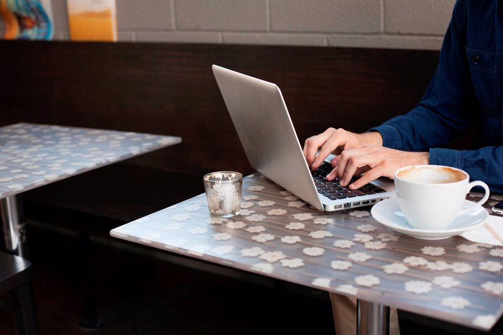 Stock Photo: 1439R-1144711 Businessman using laptop in cafe