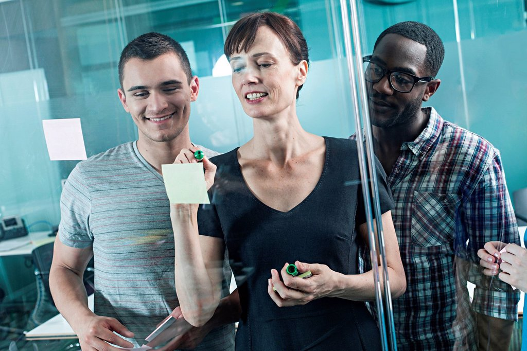Stock Photo: 1439R-1145058 Colleagues writing on adhesive notes and sticking them to window