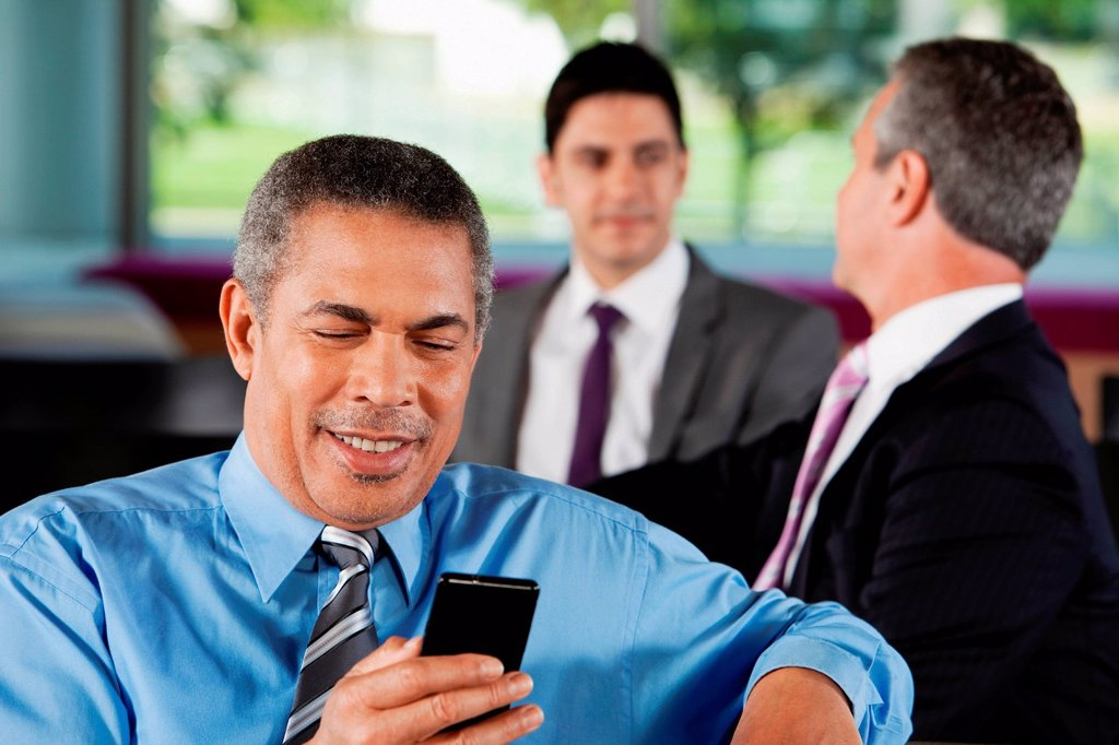 Stock Photo: 1439R-1145171 Businessman texting on smartphone
