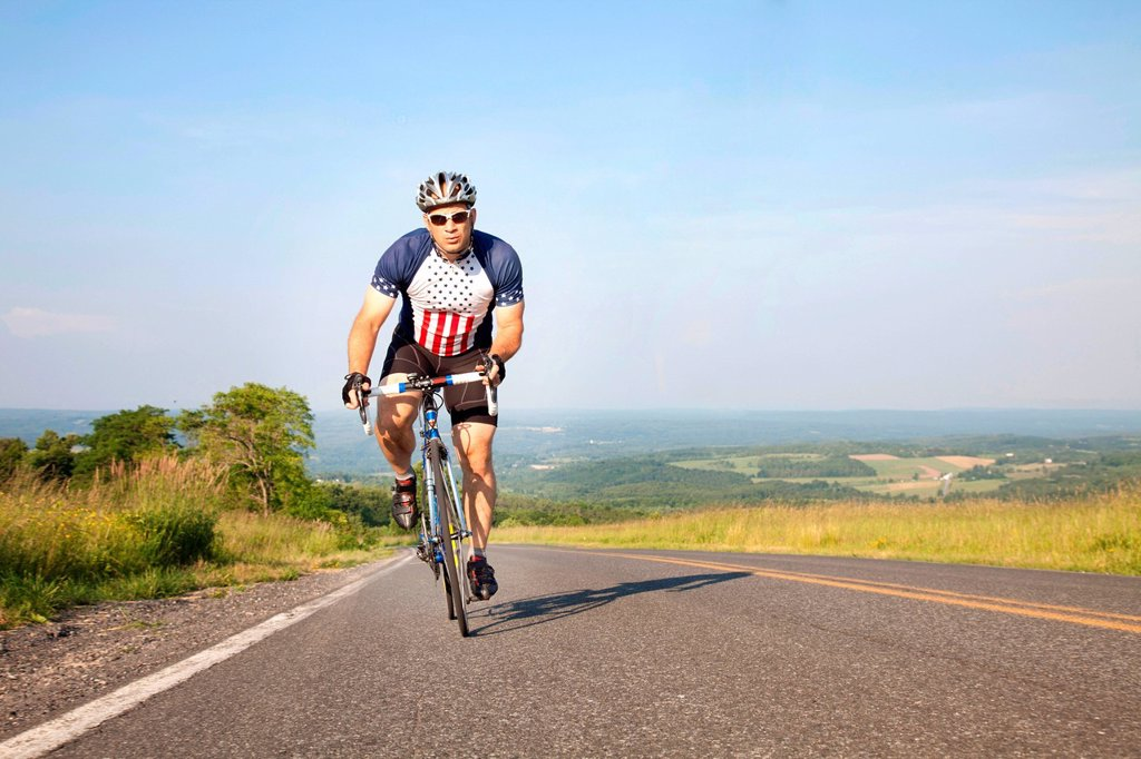 Stock Photo: 1439R-1145293 Man cycling on open road