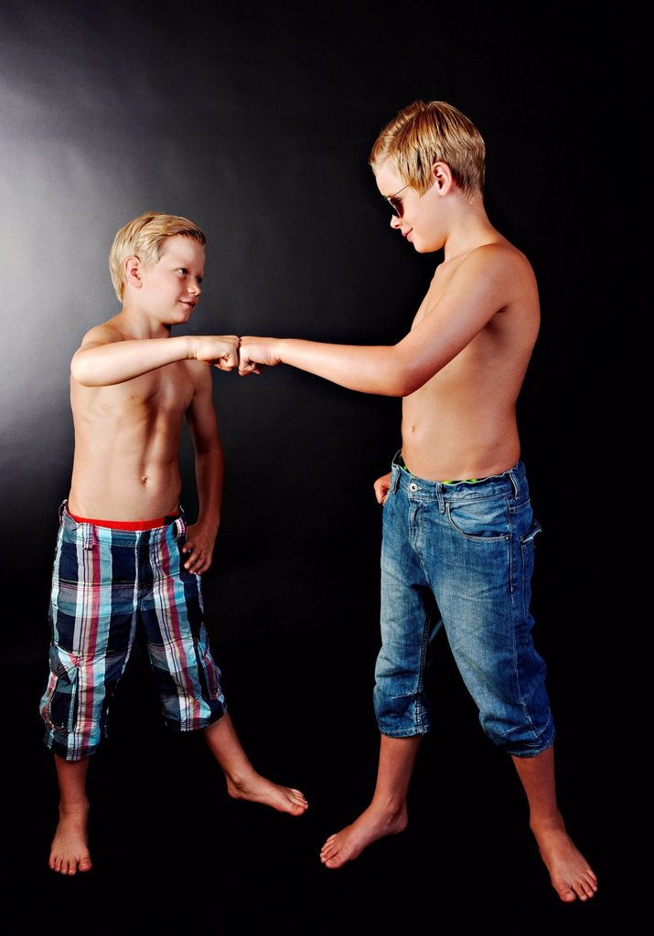 Stock Photo: 1439R-1145373 Brothers doing high five with fists