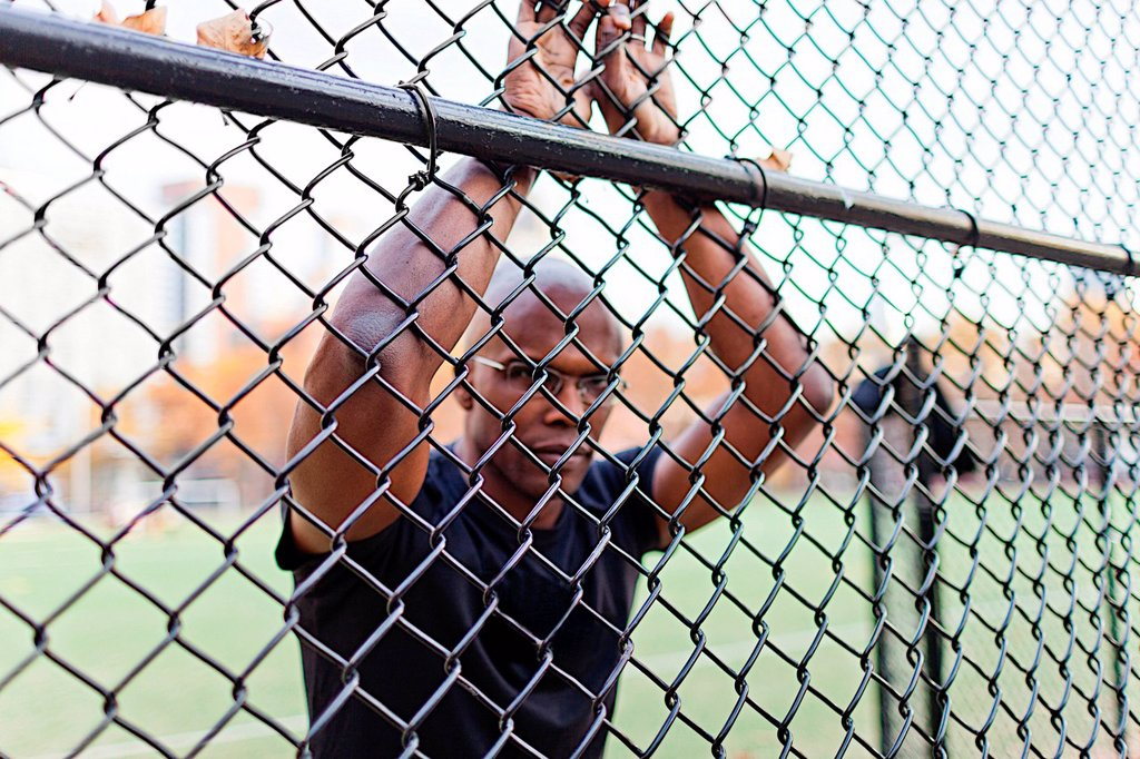 Stock Photo: 1439R-1145378 Man leaning on chain link fence