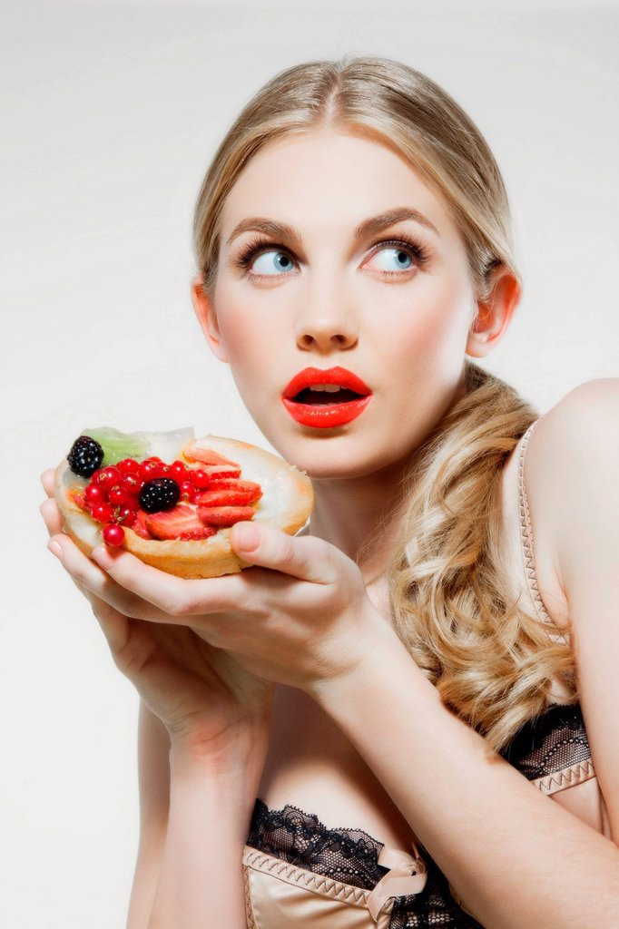 Stock Photo: 1439R-1145828 Young woman holding fresh fruit tart