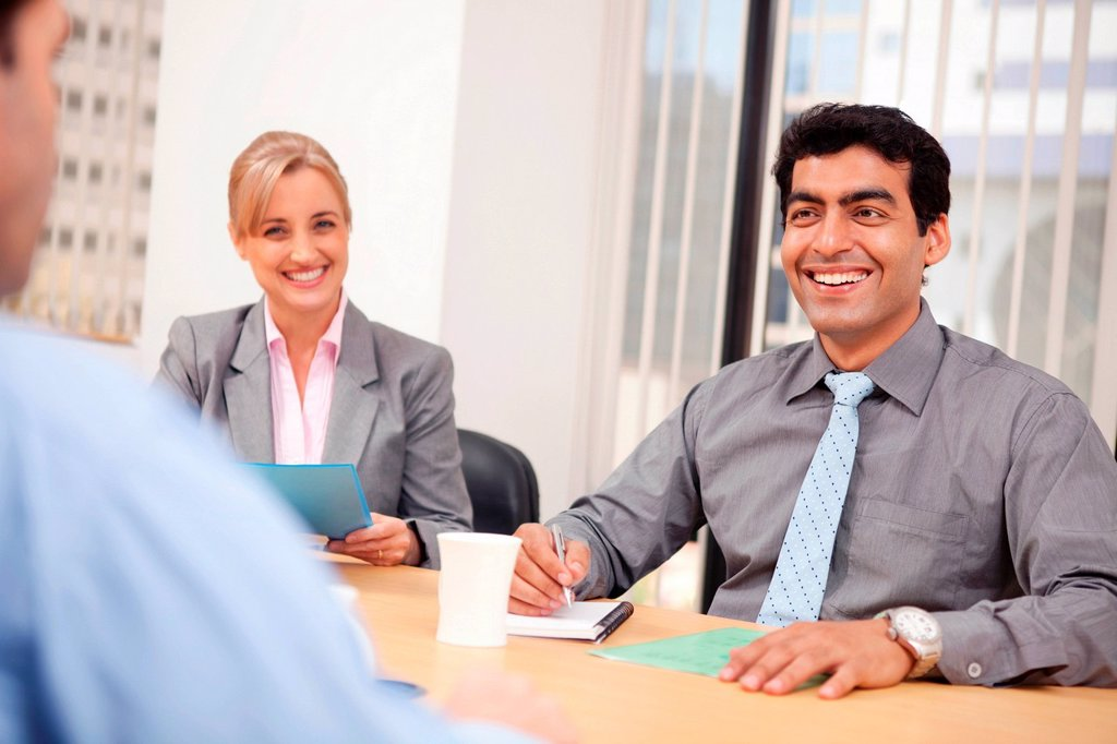 Business executives smiling in a meeting : Stock Photo