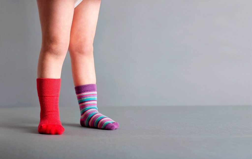Stock Photo: 1439R-1146302 Child wearing one red sock and one striped sock