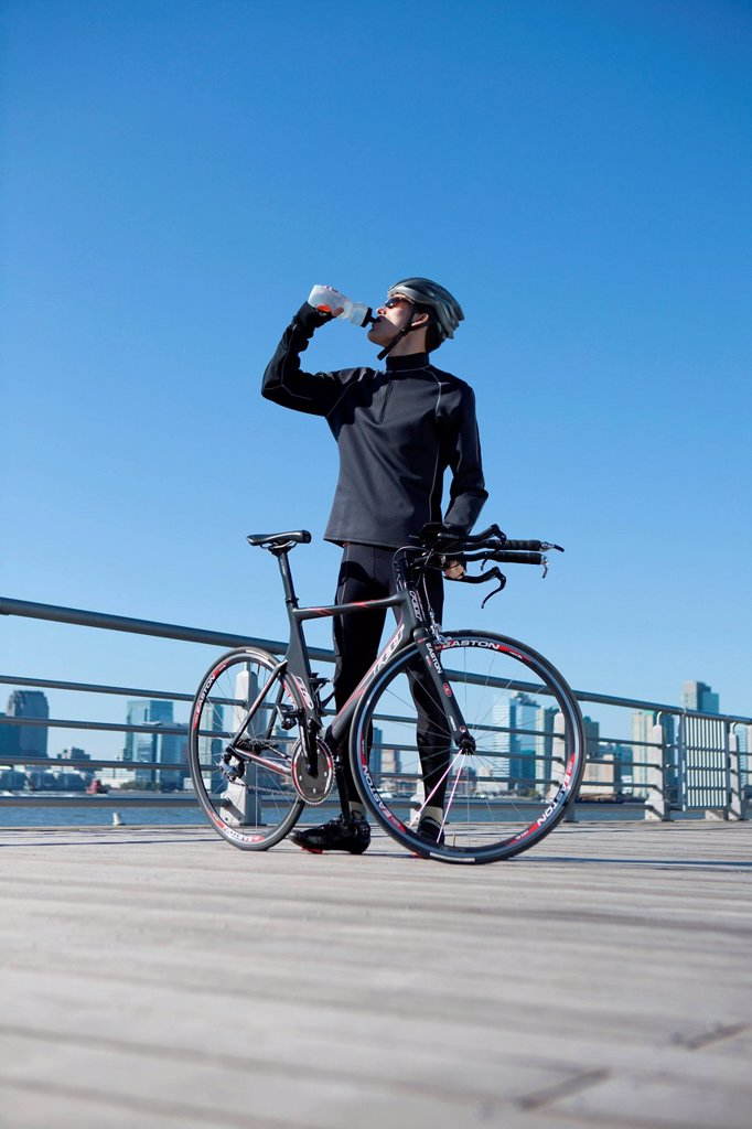 Man quenching thirst behind his racing bike : Stock Photo