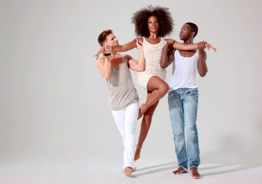 Two men holding a young woman off the ground : Stock Photo