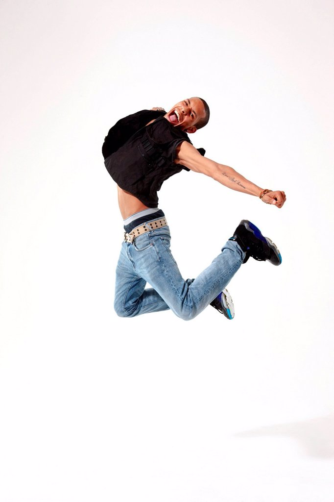 Jubilant young man in mid air : Stock Photo
