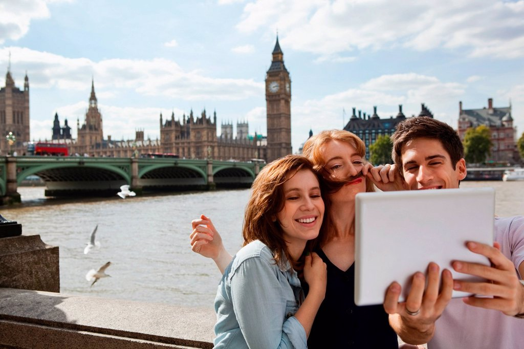 Friends using a digital tablet in central London : Stock Photo
