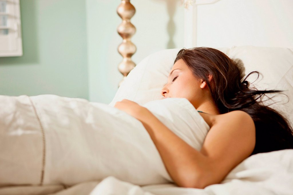 Stock Photo: 1439R-1147318 Young woman asleep in bed