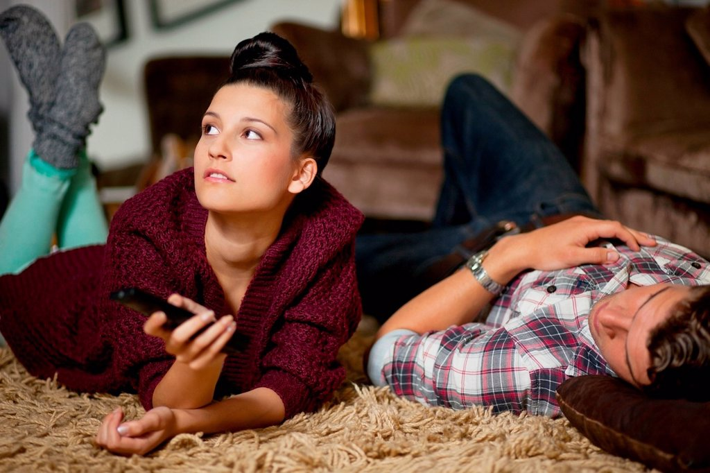 Stock Photo: 1439R-1147319 Young couple watching televsion