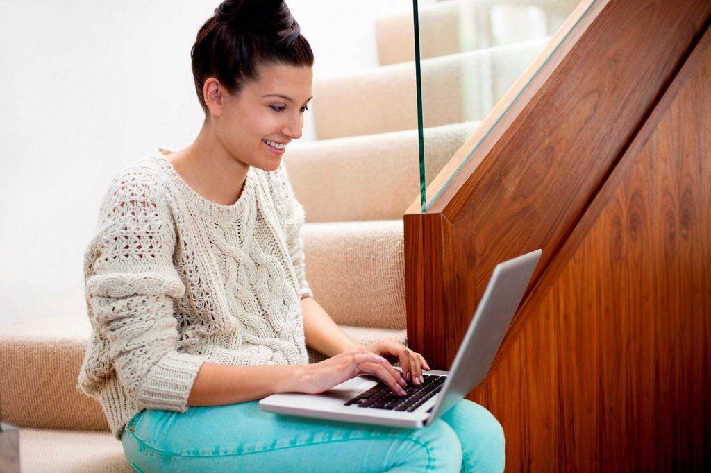 Young woman sitting on stairs using laptop : Stock Photo