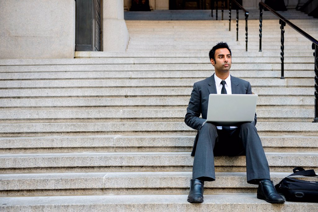 Stock Photo: 1439R-1147339 Businessman with laptop on building steps