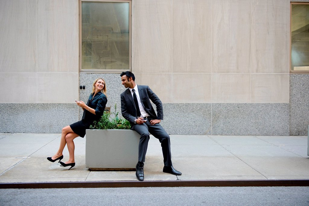 Stock Photo: 1439R-1147340 Businessman and businesswoman sitting outdoors, looking at each other