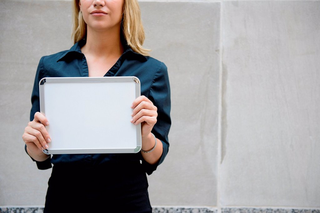 Businesswoman holding a blank sign : Stock Photo