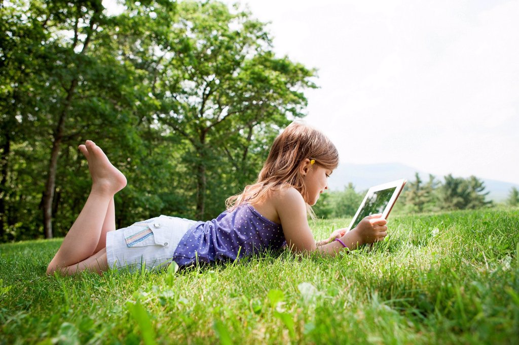 Girl lying on grass with digital tablet : Stock Photo