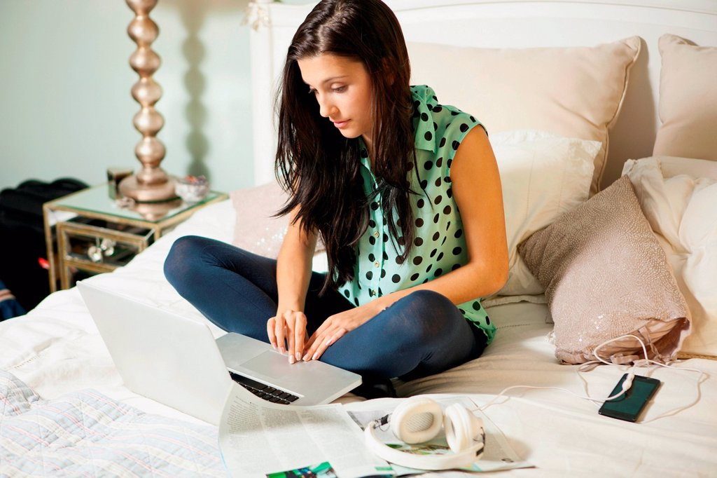 Stock Photo: 1439R-1147385 Young woman on bed with laptop