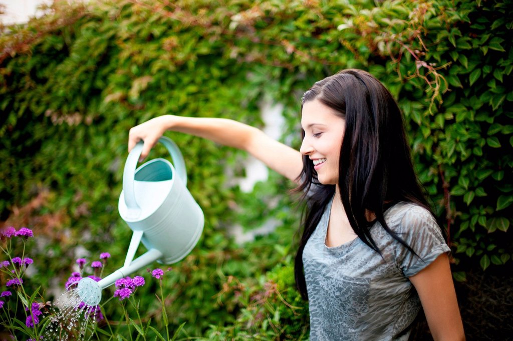 Stock Photo: 1439R-1147390 Young woman watering flowers in garden