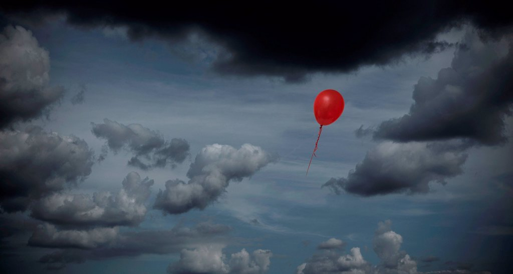 Stock Photo: 1439R-1147428 Red balloon floating through dark sky