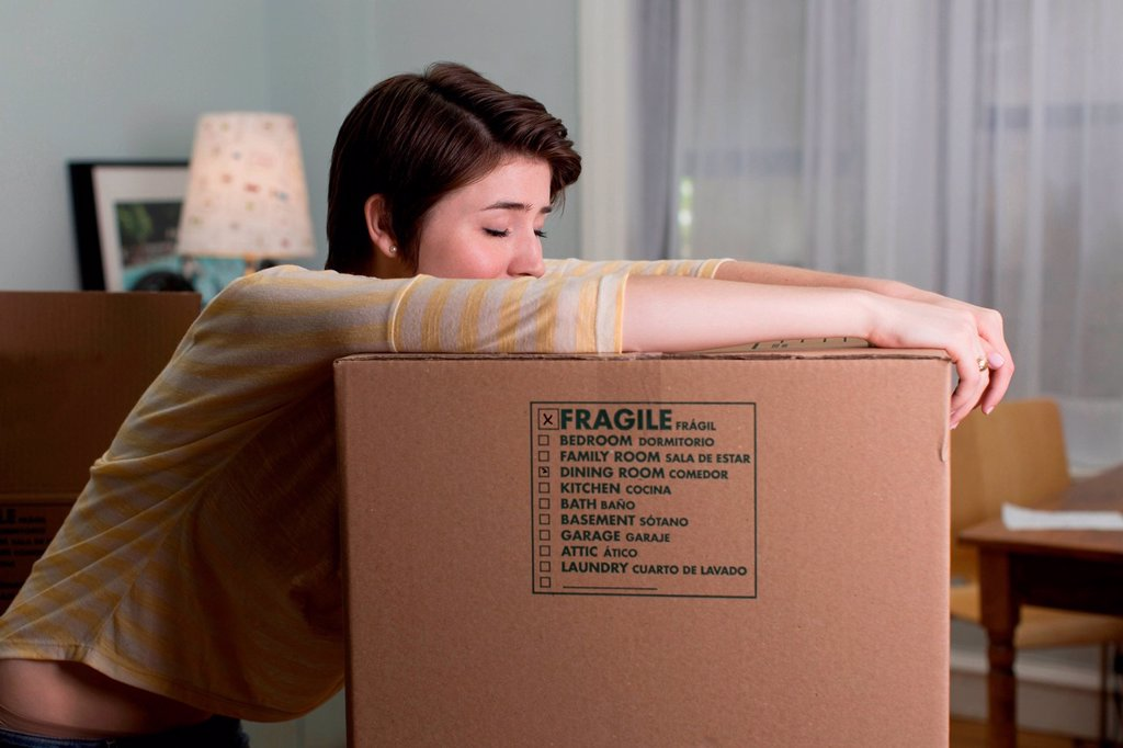 Stock Photo: 1439R-1147435 Tired young woman resting on moving box