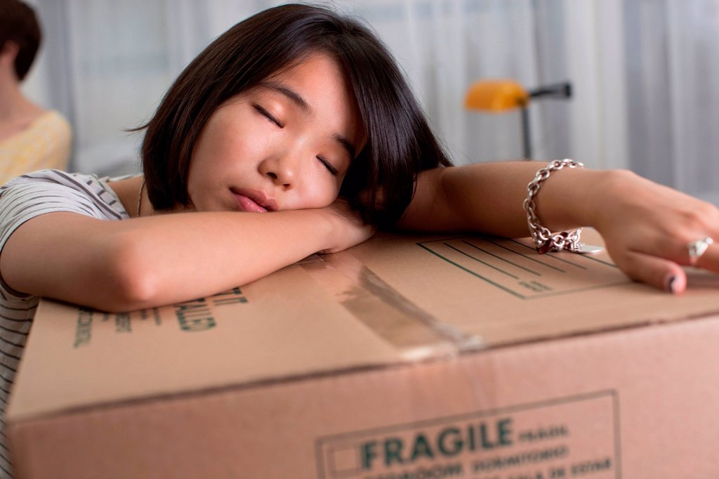 Stock Photo: 1439R-1147436 Tired young woman resting on moving box