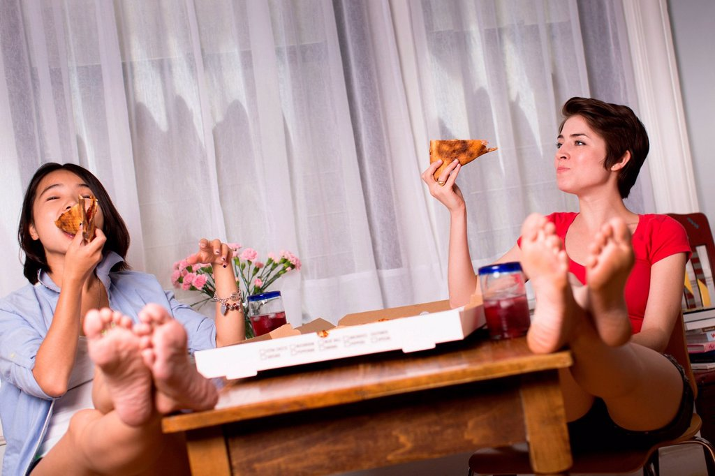 Stock Photo: 1439R-1147440 Female friends enjoying takeaway pizza