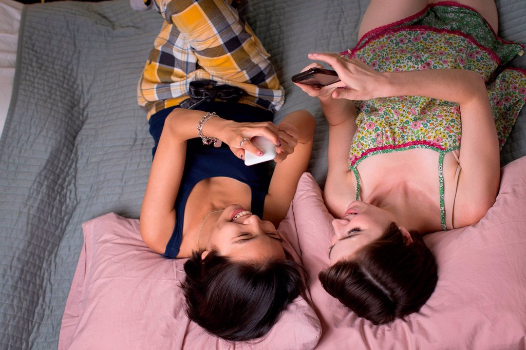 Young women lying on bed, looking at cellphones, overhead view : Stock Photo