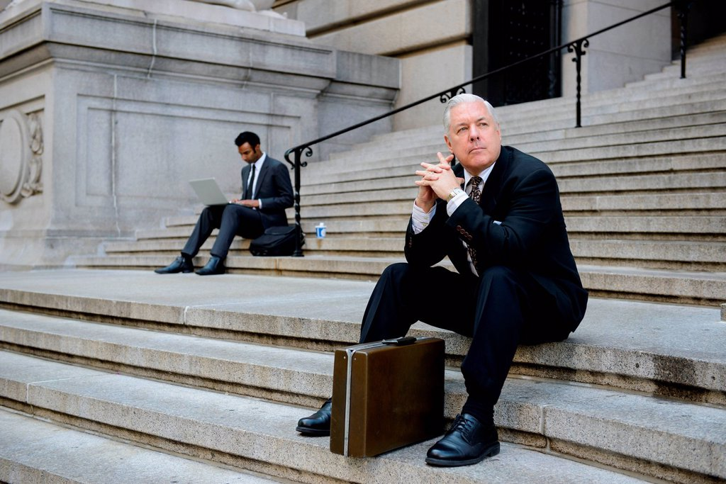 Businessmen sitting on building steps : Stock Photo