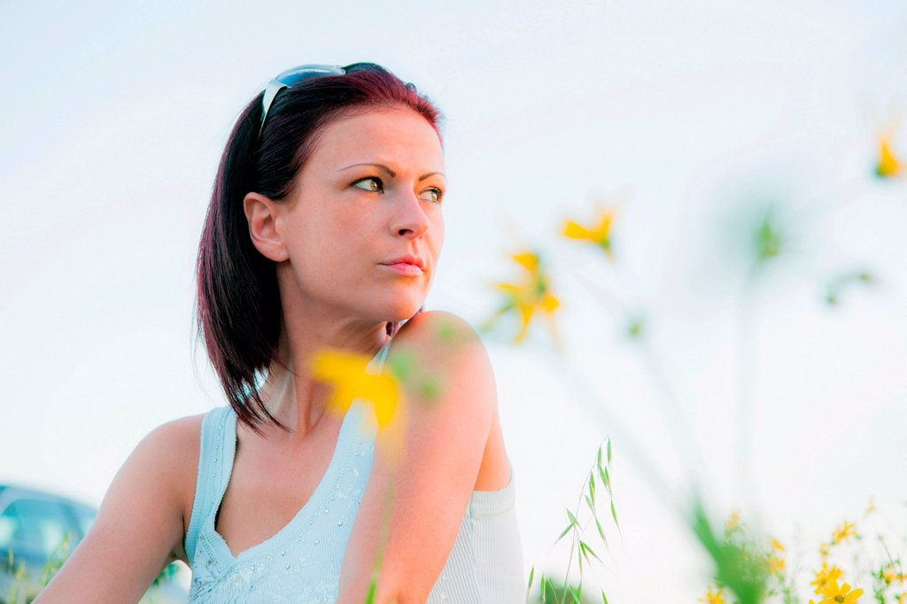 Woman in field of flowers, looking away : Stock Photo