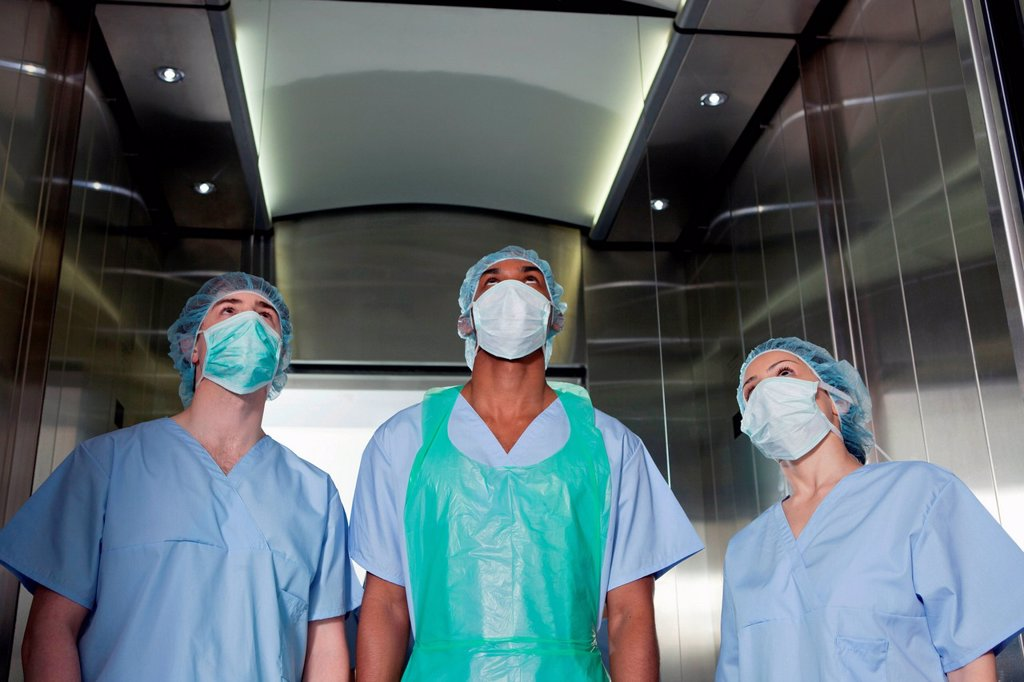 Three surgeons in hospital elevator : Stock Photo