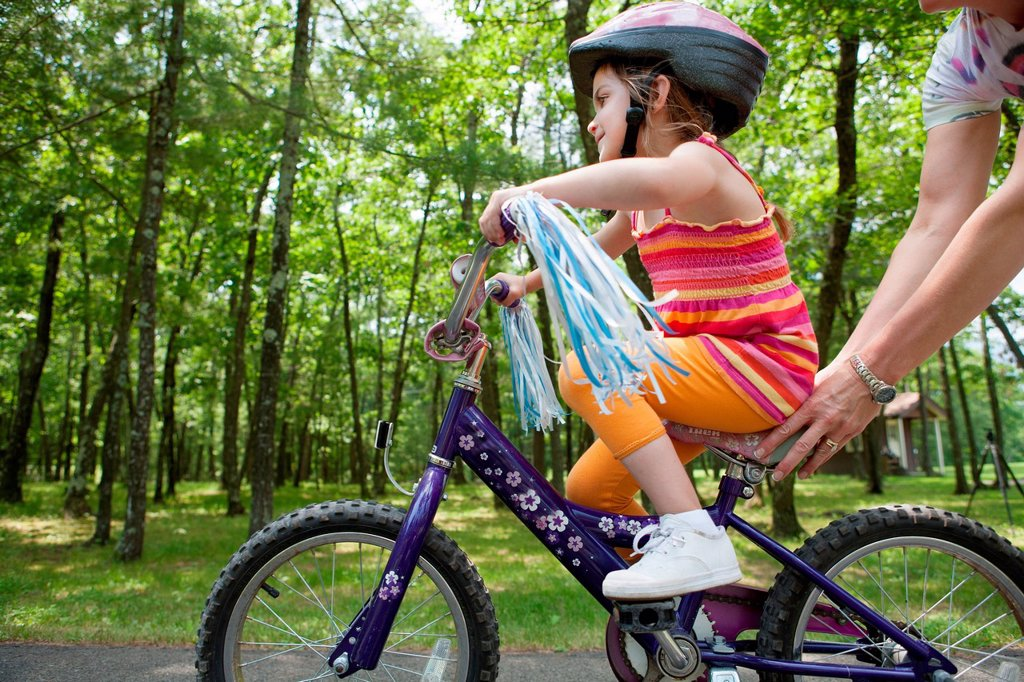 Stock Photo: 1439R-1147515 Mother helping daughter to ride bicycle