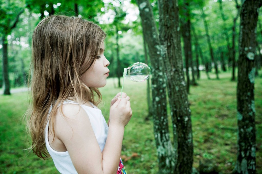 Girl blowing bubbles in forest : Stock Photo