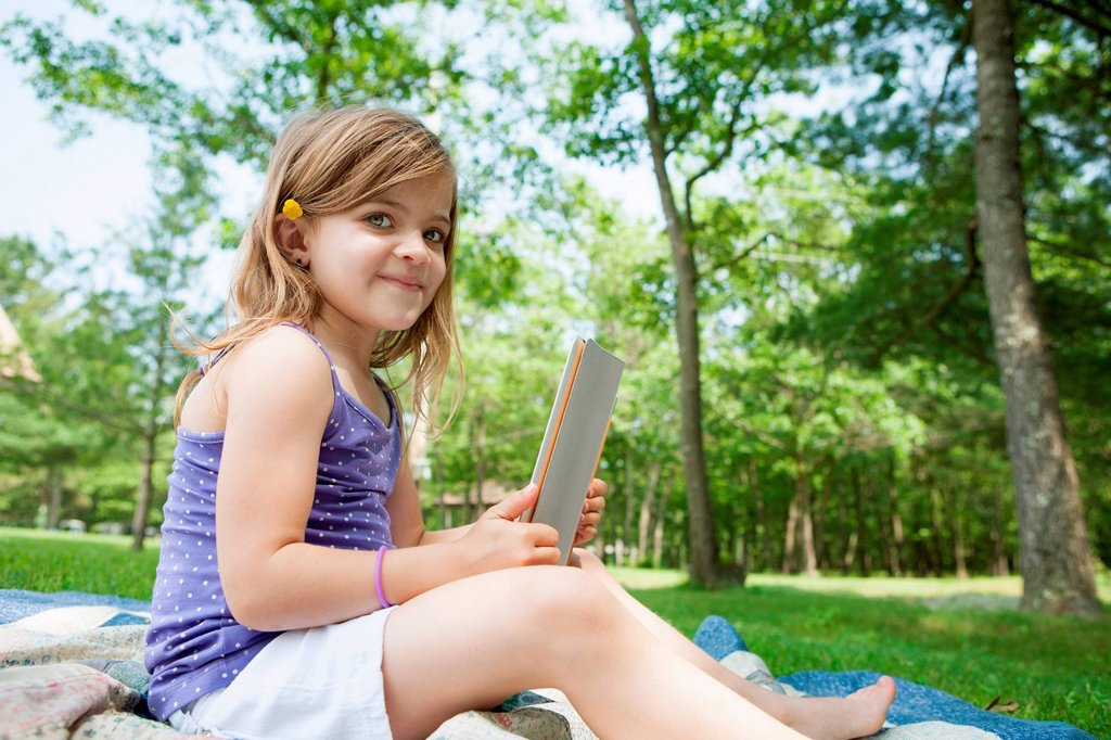 Stock Photo: 1439R-1147532 Girl sitting on picnic blanket with digital tablet