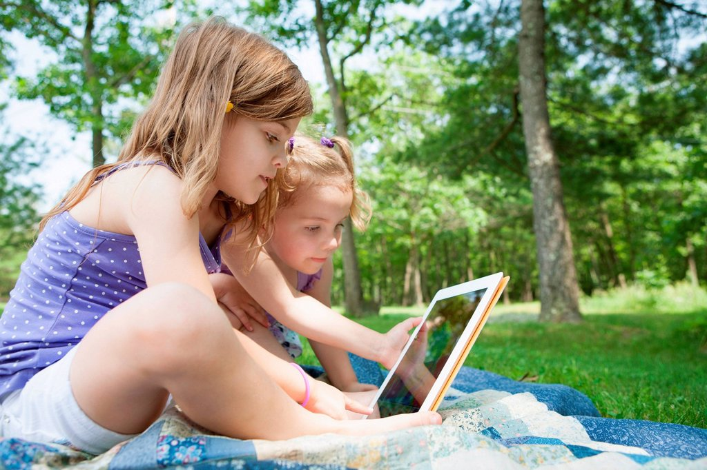 Two girls sitting on picnic blanket with digital tablet : Stock Photo