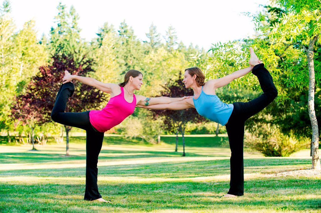Stock Photo: 1439R-1147536 Two women supporting each other in yoga pose in a park