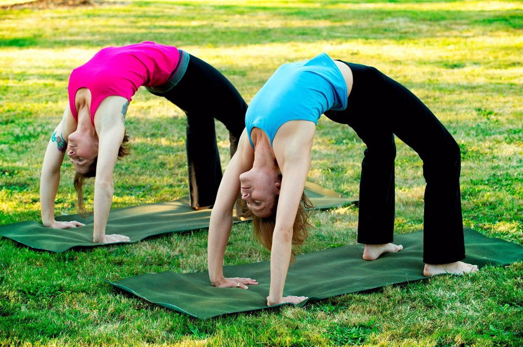 Stock Photo: 1439R-1147538 Two women bending over backwards on yoga mats outdoors