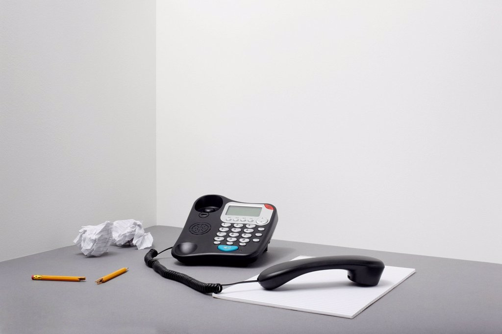 Stock Photo: 1439R-1147560 Landline office phone off the hook with pencil and paper
