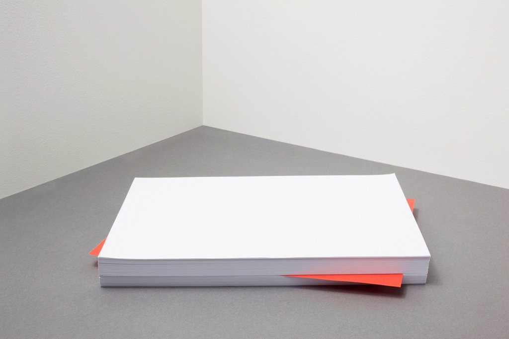 Stock Photo: 1439R-1147568 Red piece of paper amongst stack of blank paper
