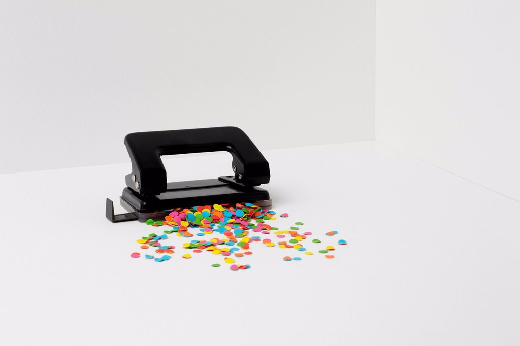 Stock Photo: 1439R-1147577 Hole puncher with multi coloured paper
