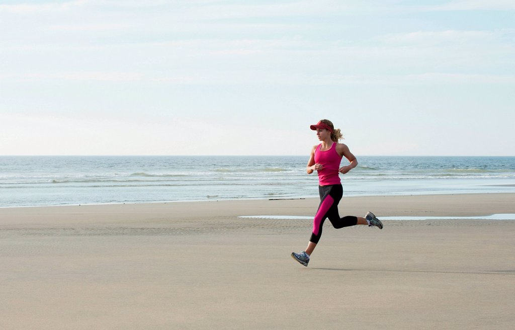 Stock Photo: 1439R-1147580 Young woman running on beach