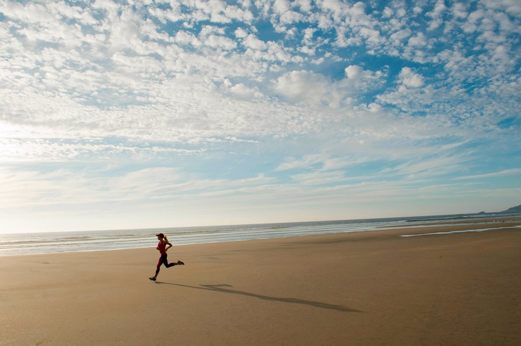 Young woman running on beach : Stock Photo
