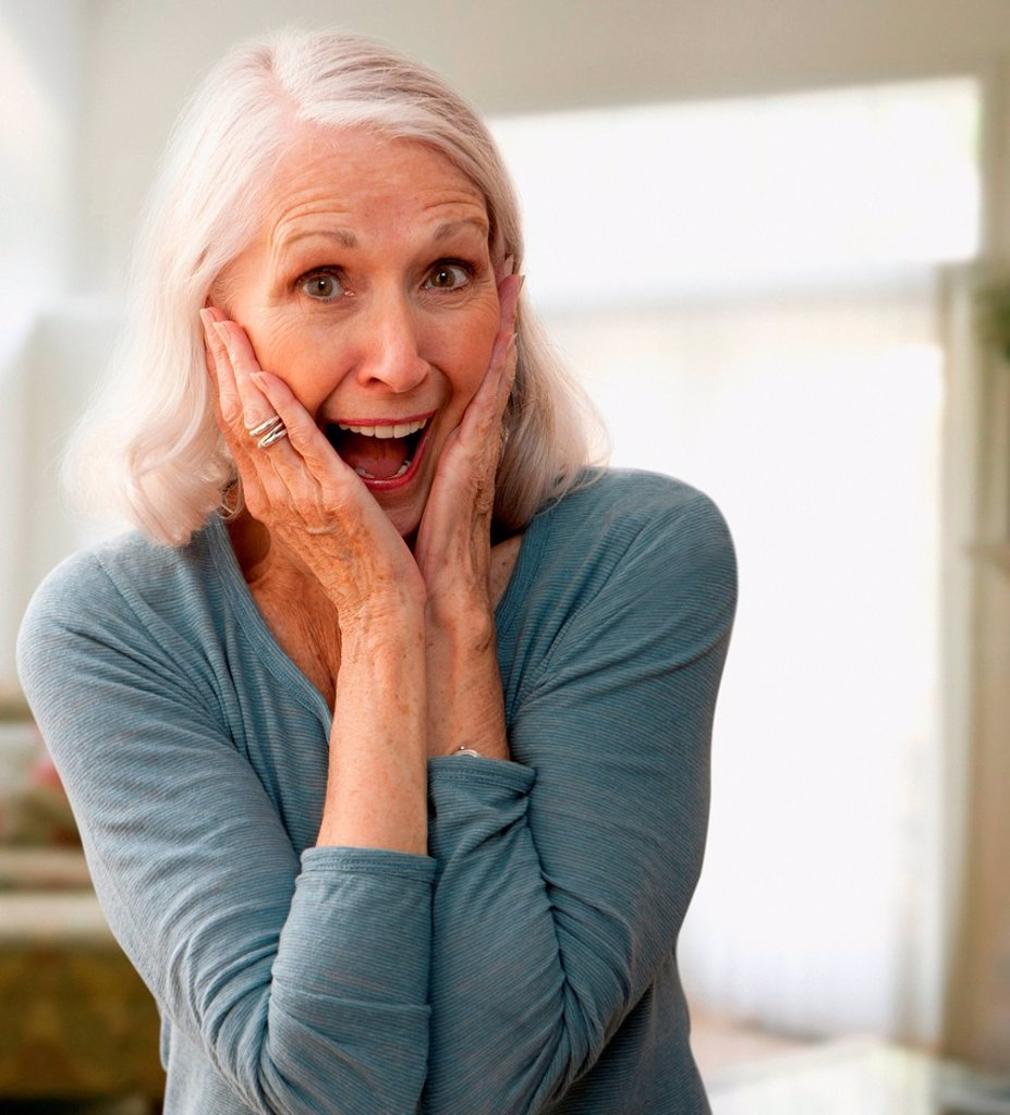 Stock Photo: 1439R-1147583 Senior woman gasping with mouth open, touching face