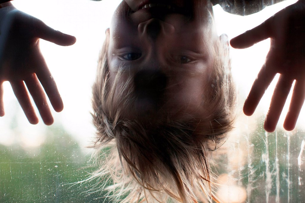 Stock Photo: 1439R-1147588 Boy looking through window, upside down
