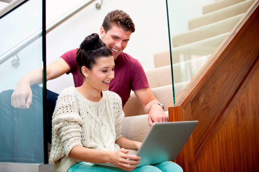 Stock Photo: 1439R-1147599 Young couple with laptop