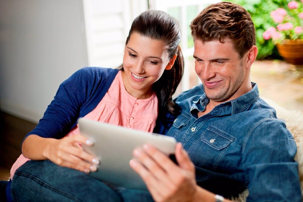 Stock Photo: 1439R-1147610 Young couple with digital tablet