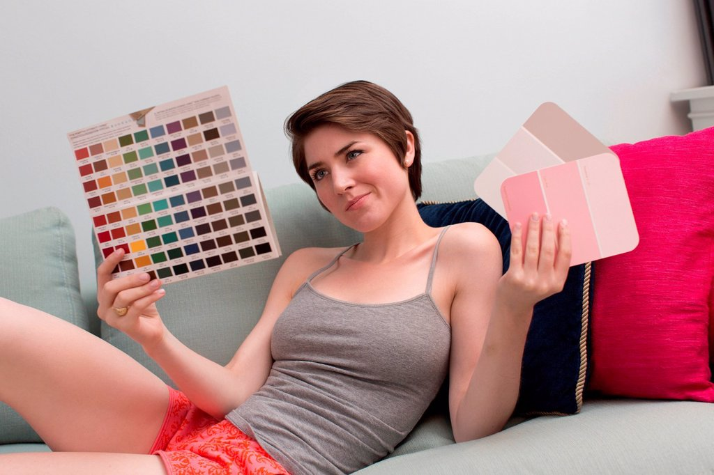 Stock Photo: 1439R-1147660 Young woman on sofa, looking at color swatches
