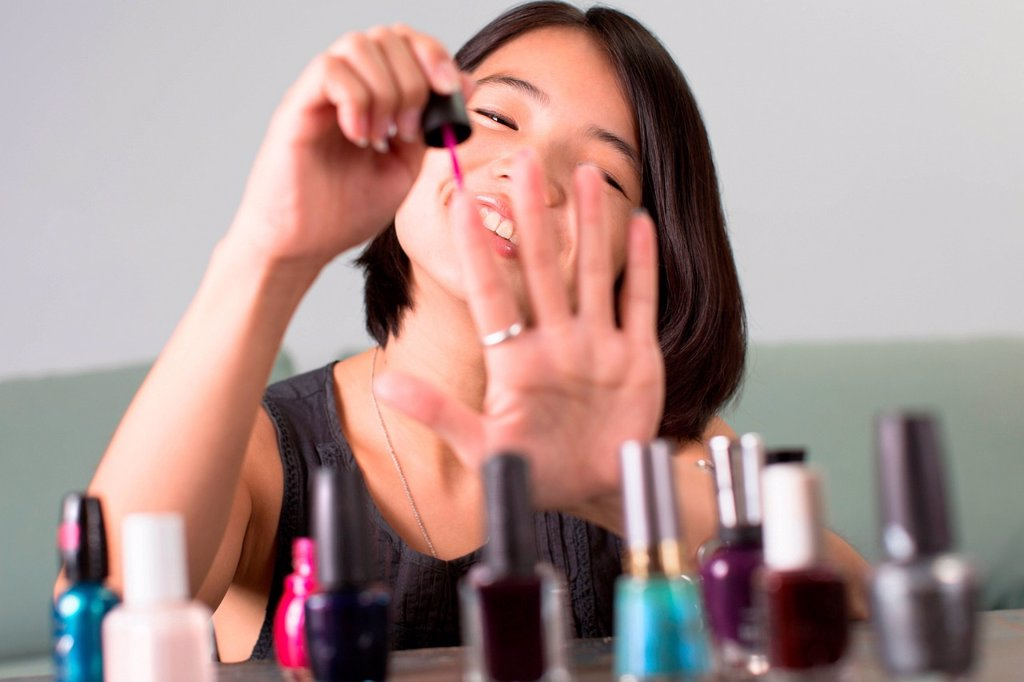 Young woman painting her fingernails : Stock Photo