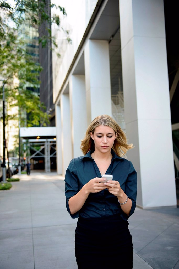 Businesswoman walking and texting on cellphone : Stock Photo