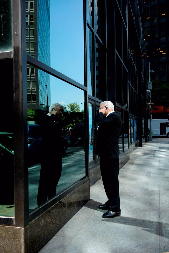 Stock Photo: 1439R-1147677 Businessman looking at reflection in building window