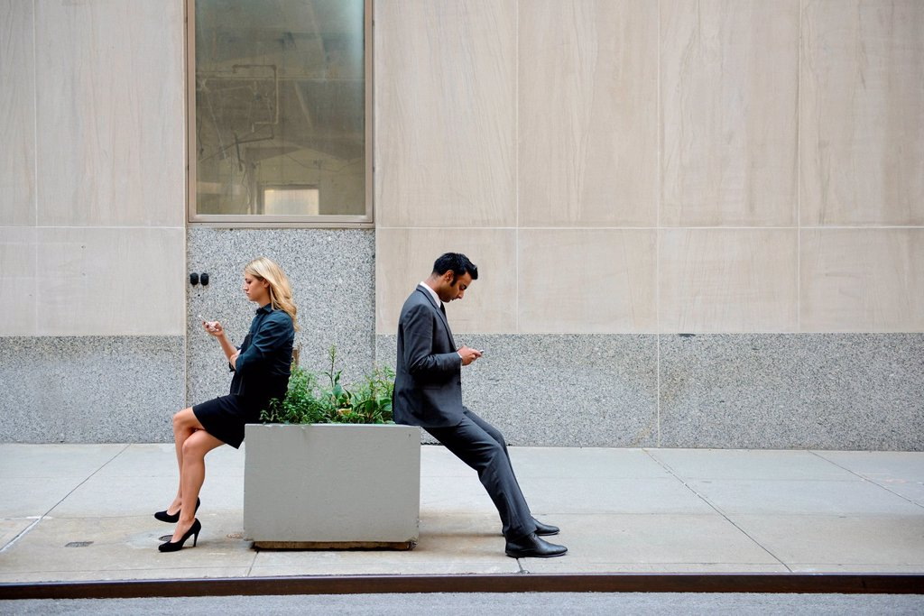 Businesspeople sitting and looking at cellphones outdoors : Stock Photo
